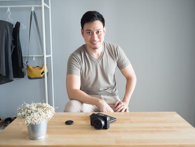 Homem asiático em sua oficina com uma câmera mirrorless na mesa de madeira.