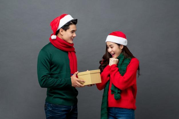 Homem asiático em traje de natal surpreender sua namorada com presente