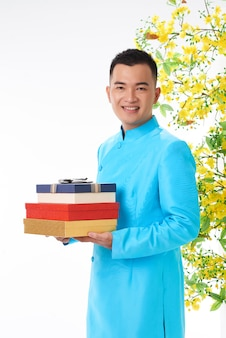 Homem asiático em traje tradicional segurando caixas de presente para sua família