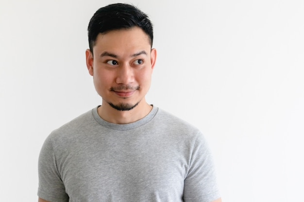Homem asiático em uma camiseta cinza está olhando para o espaço vazio na parede branca isolada.