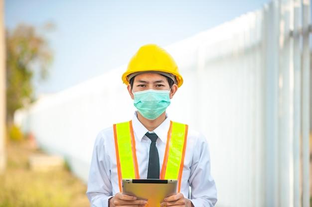 Homem asiático, engenheiro, máscara facial, segurando, telefone móvel, dispositivo, tecnologia, trabalho, ligado, construção local