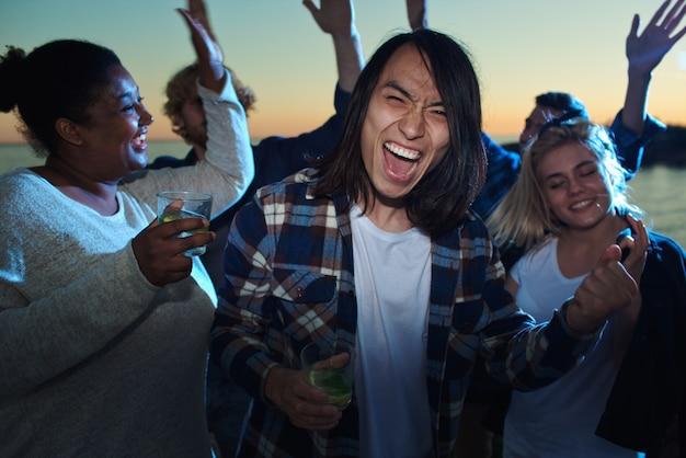 Homem asiático entre amigos dançando