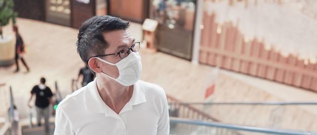 Homem asiático envelhecido médio usando óculos e máscara médica, surto de coronavírus wuhan, poluição do ar e conceito de saúde