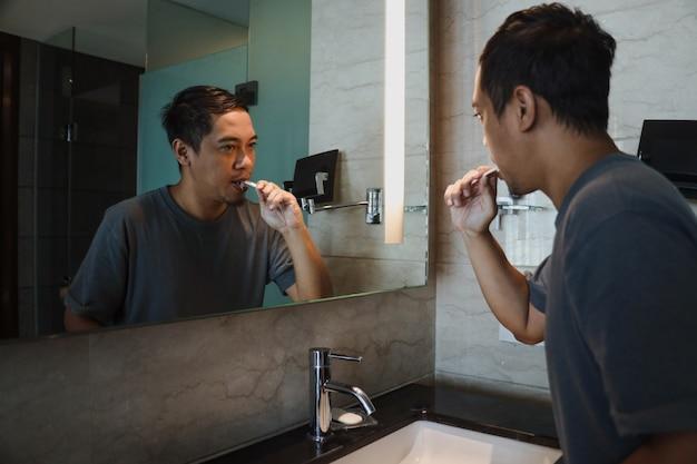 Homem asiático escovando os dentes e olhando no espelho no banheiro