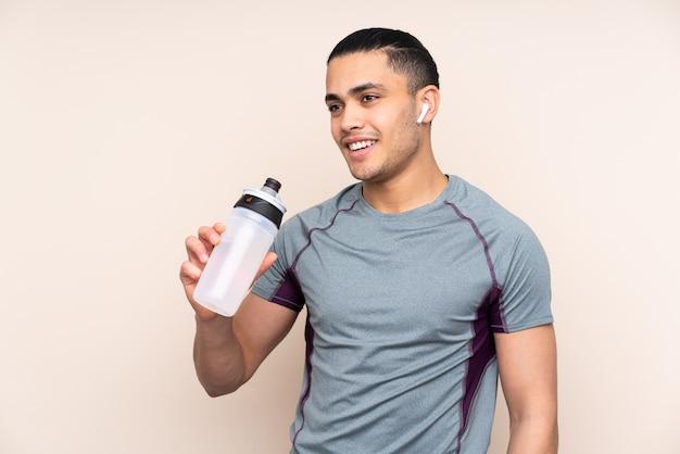 Homem asiático esporte na parede bege com garrafa de água de esportes