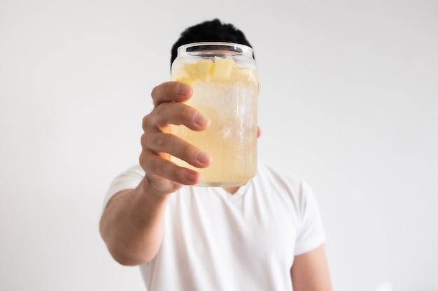 Homem asiático está bebendo refrigerante de limão gelado na parede branca isolada.