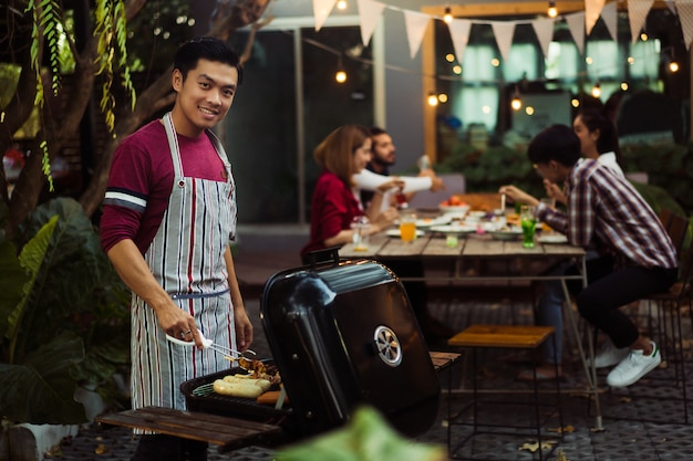 Homem asiático está cozinhando para um grupo de amigos para comer churrasco