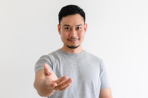 Homem asiático está fazendo um gesto de convite ou oferece ajuda.