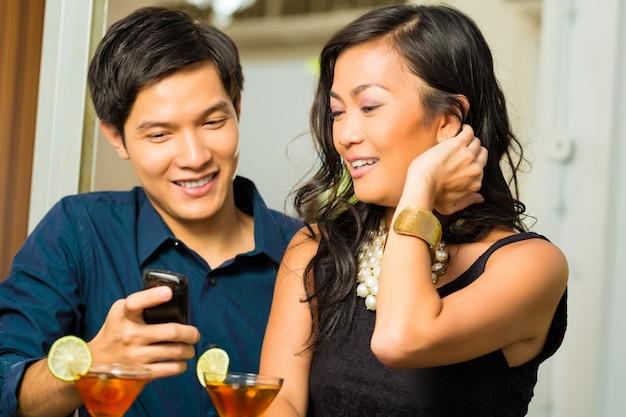 Homem asiático está flertando com a mulher no bar