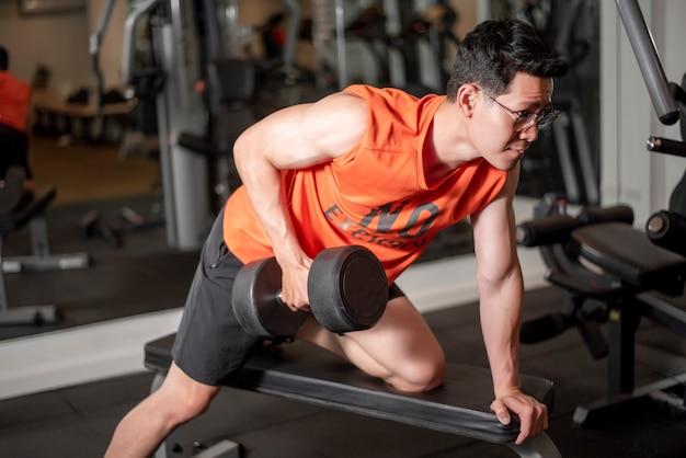 Homem asiático está malhando na academia de fitness