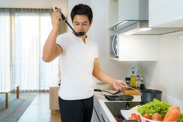 Homem asiático está usando uma concha para engrossar a sopa de legumes em uma panela na cozinha de casa.