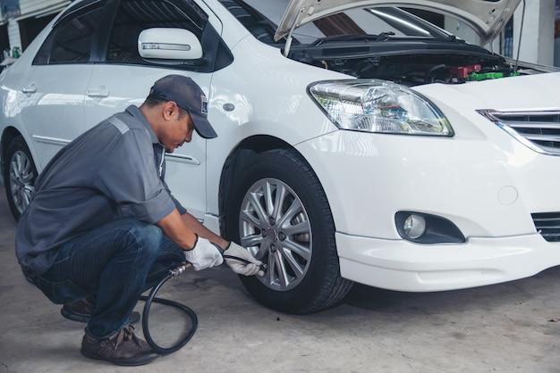 Homem asiático está verificando o pneu do carro para o serviço de manutenção automotiva. mecânico de automóveis inflar o pneu na garagem.