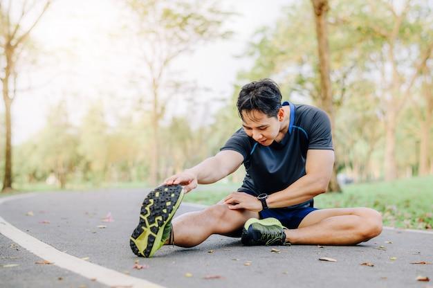 Homem asiático, esticando a perna na pista de corrida no parque