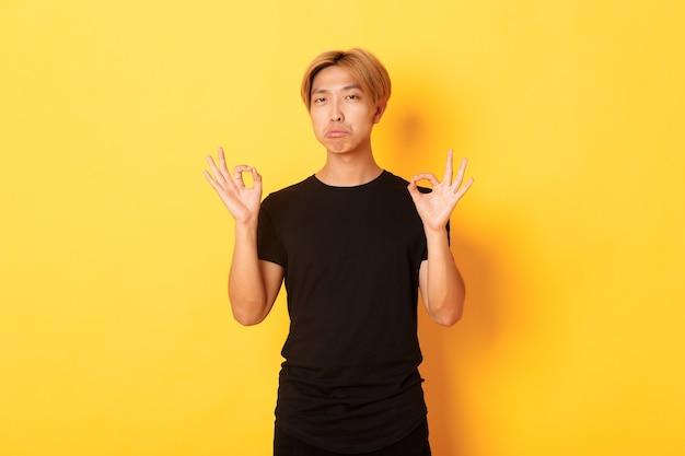 Homem asiático estiloso impressionado com cabelo loiro, mostrando um gesto de aprovação e elogiando algo bom, em pé na parede amarela