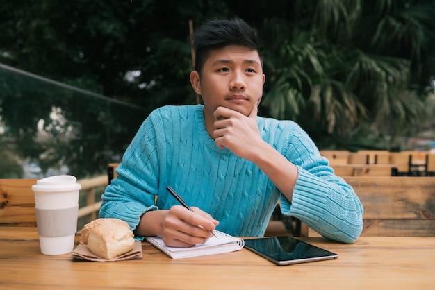 Homem asiático estudando em uma cafeteria.