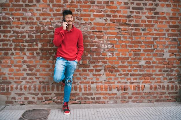 Homem asiático falando ao ar livre ao telefone.
