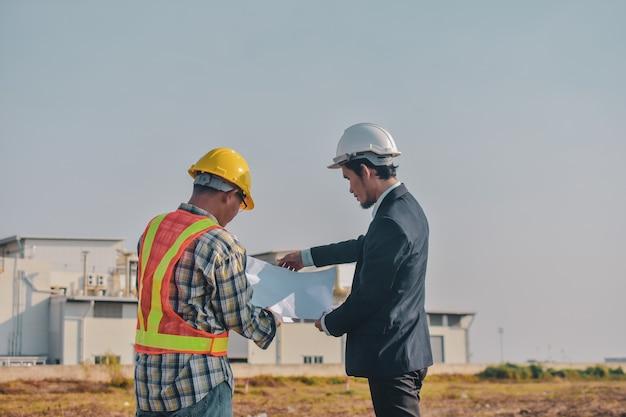 Homem asiático falando de negócios ao ar livre na construção do local