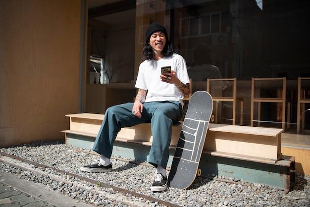 Homem asiático fazendo uma pausa no skate