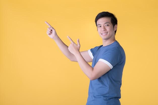 Homem asiático feliz apontando os dedos para o espaço vazio da cópia do texto sobre fundo amarelo