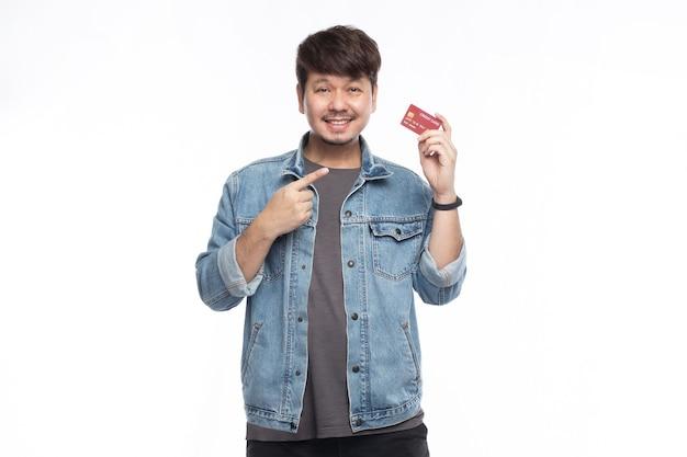 Homem asiático feliz com o rosto sorridente segurando um cartão de crédito e apontando o dedo para o cartão de crédito