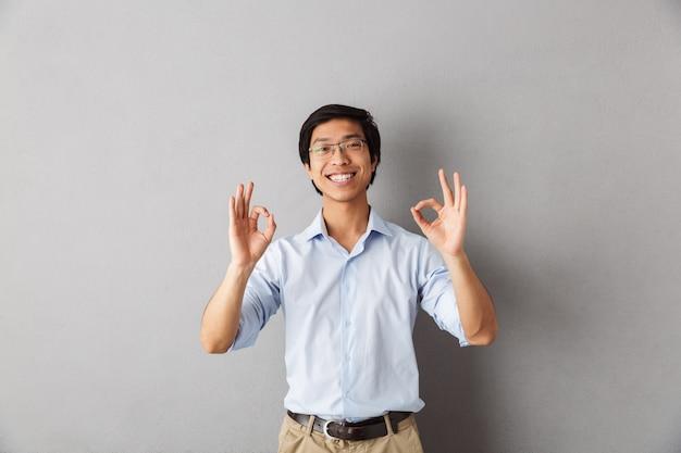 Homem asiático feliz em pé isolado, mostrando-se bem
