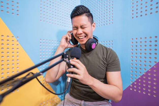 Homem asiático feliz está gravando um podcast em seu estúdio
