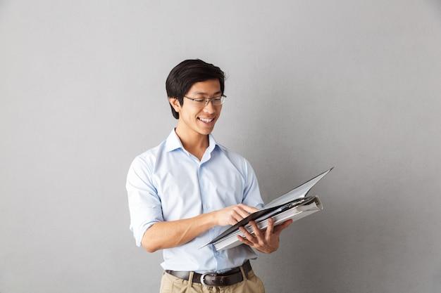 Homem asiático feliz, isolado, carregando pastas com documentos