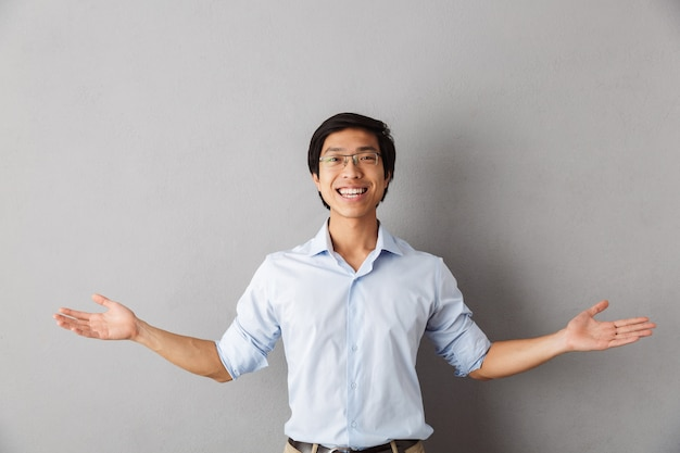 Homem asiático feliz, isolado, com as mãos estendidas