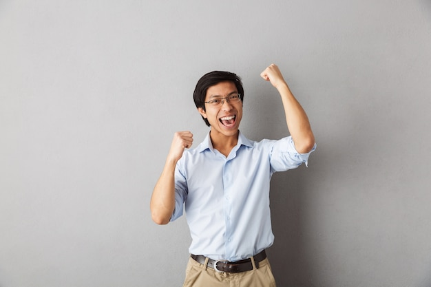 Homem asiático feliz, isolado, comemorando