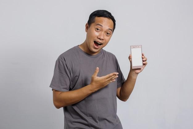 Homem asiático feliz mostrando seu telefone inteligente com tela em branco para simulação
