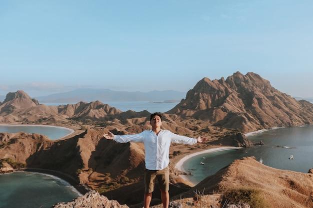 Homem asiático feliz parado no topo da colina da ilha padar