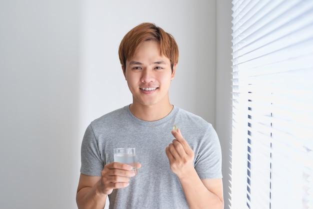 Homem asiático feliz segurando pílula de vitamina ômega 3 em casa