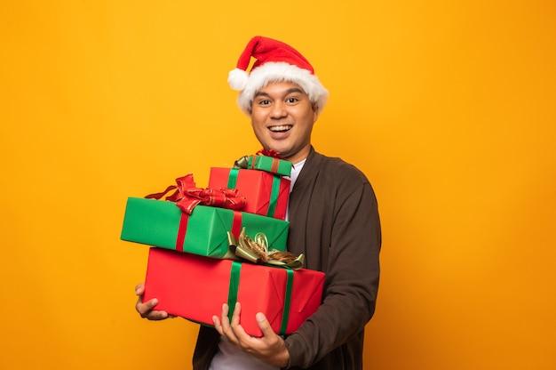 Homem asiático feliz segurando presentes de natal