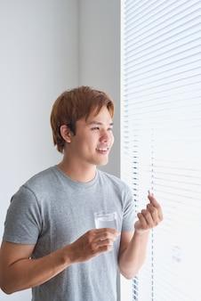 Homem asiático feliz segurando um comprimido e um copo d'água olhando para a câmera