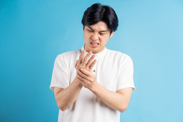 Homem asiático fica chateado com a dor na palma da mão