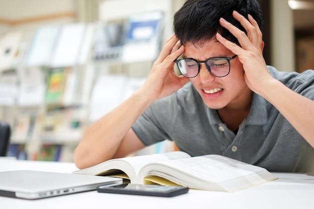 Homem asiático, ficando sério após ler livros para teste na biblioteca