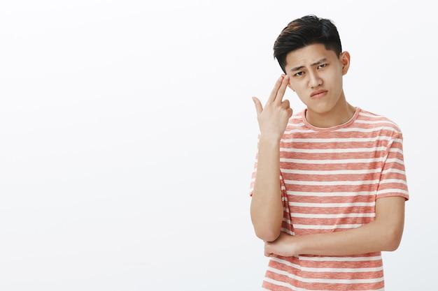 Homem asiático fofo sombrio sofrendo de tédio, sentindo-se chateado e irritado, mostrando gesto de arma perto do templo, sobrancelha ouvindo e fazendo careta de tristeza e sentimento entediante
