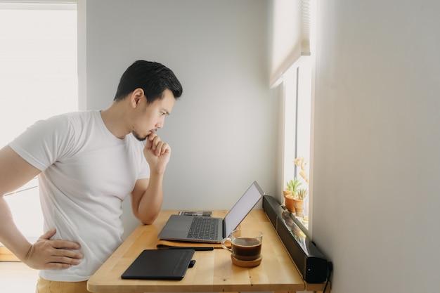 Homem asiático freelancer está pensando e trabalhando em seu laptop
