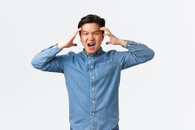 Homem asiático furioso e angustiado, parecendo furioso e frustrado, perdendo a paciência, segurando as mãos na cabeça e franzindo a testa com raiva, perdendo o controle sobre as emoções, sentindo raiva e raiva, fundo branco.