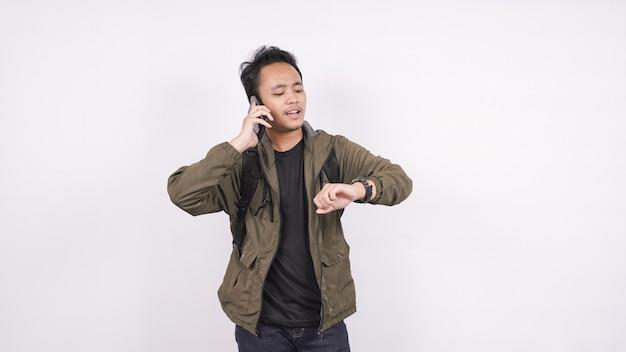 Homem asiático gritou enquanto olhava para um relógio em um espaço em branco