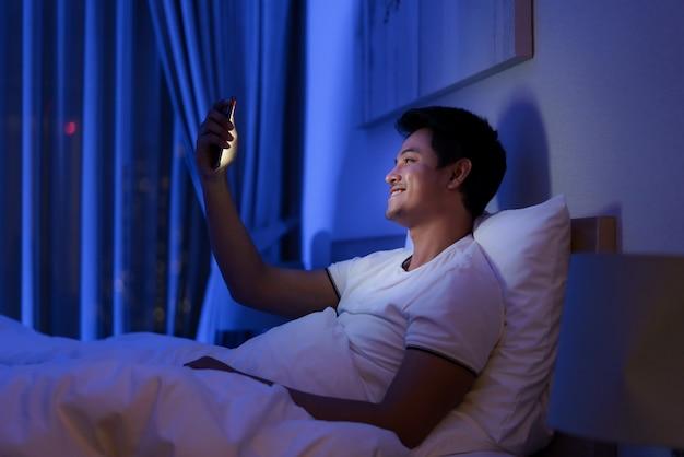 Homem asiático, happy hour virtual, reunião on-line com a namorada em videoconferência até boa noite antes de dormir com smartphone para reunião on-line em videochamada