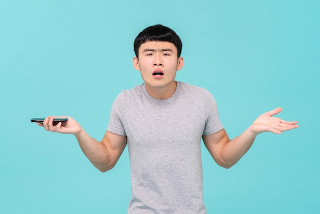 Homem asiático infeliz tendo problemas com seu smartphone