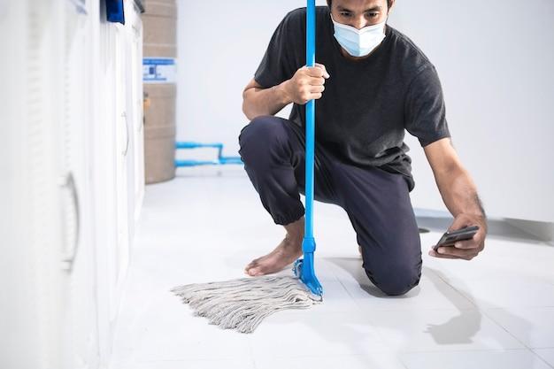 Homem asiático inspecionando equipe de limpeza na cozinha, banheiro embaçado