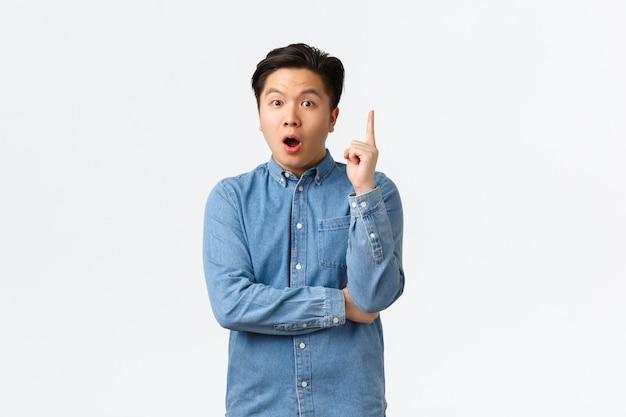 Homem asiático inteligente e criativo animado na camisa, tendo a ideia. cara fazendo sugestão, pense em um grande plano, levantando o dedo indicador em um gesto de eureka, dizendo sua opinião, fundo branco de pé.