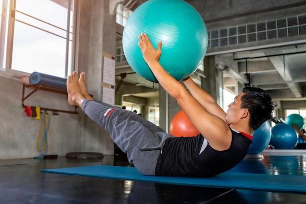 Homem asiático inteligente no sportswear treinando os músculos abdominais com ginásio bola na aptidão.