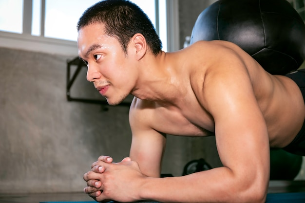 Homem asiático inteligente no sportswear treinando os músculos abdominais com tábuas no ginásio de fitness.