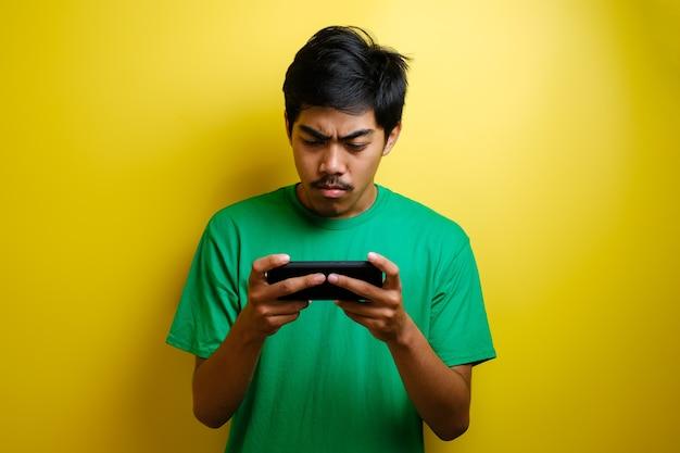 Homem asiático joga jogo para celular em seu smartphone com uma expressão séria ou zangada contra um fundo amarelo