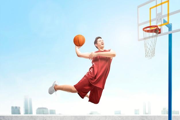 Homem asiático jogador de basquete pula no ar com a bola tentando marcar