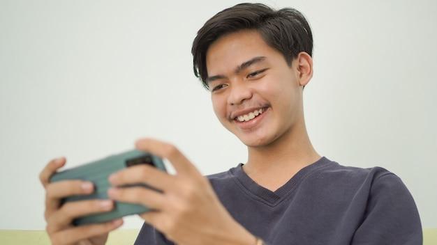 Homem asiático jogando em casa alegremente