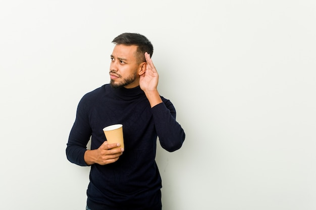 Homem asiático jovem de raça mista segurando um café para viagem, tentando ouvir uma fofoca.